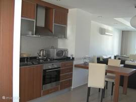 De kok houdt altijd contact met degene die in de woonkamer  of op het terras zijn.