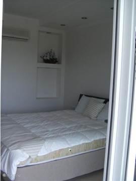 Zicht op  het master bed vanaf het terras. Boven het master bed zijn er dimbare spots.