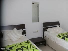 Tweede slaapkamer met twee bedden, spiegel, nachtkastje en 3 inbouw kleerkasten. Rechtstreeks via een schuifpui verbonden met het derde terras.