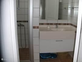 De twee badkamers omvatten elk een lavabo, spiegel, kastje, douche met glazen deuren en hangtoilet+ nodige accessoires.