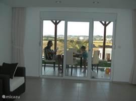 Van de keuken kijk je zo doorheen de woonkamer op het  terras en landschap.