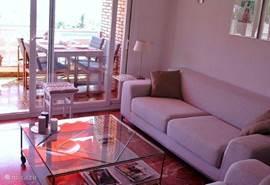 De zithoek in de woonkamer met twee komfortabele banken en toegang tot het terras.