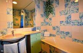 De badkamer in de typische Portugese stijl, voorzien van bad, douche en wastafelmeubel.