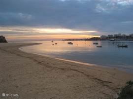 Het nabij gelegen strand bij het vallen van de avond.