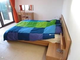 Modern ingerichte slaapkamer met nieuw twee persoonsbed met schuifpui naar overdekt terras aan het zwembad.