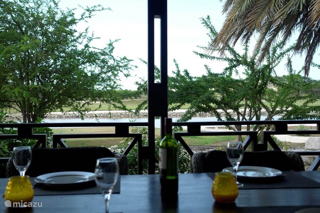 Uitzicht vanaf uw eettafel op meer met flamingo's en golfbaan
