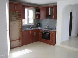 Open keuken (koelkast, oven, koffiezetapparaat) met 6 persoons eettafel en stoelen en  aansluitend de woonkamer.