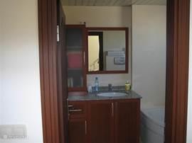 Badkamer met badmeubel en hoek/zitbad en toilet.