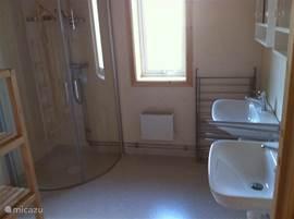 badkamer met twee wastafels en douchekabine