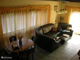 Ruime woonkamer met zithoek, eethoek en openslaande deuren naar de veranda. Alle raampartijen zijn voorzien van luxaflex en vitrage. De vloer op de begane grond heeft plavuizen.