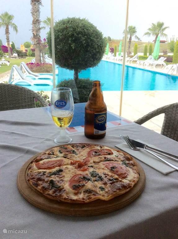 Mooi uitzicht op het zwembad vanuit de Babylon Bar & Restaurant terwijl u een lekkere Italiaanse pizza eet.