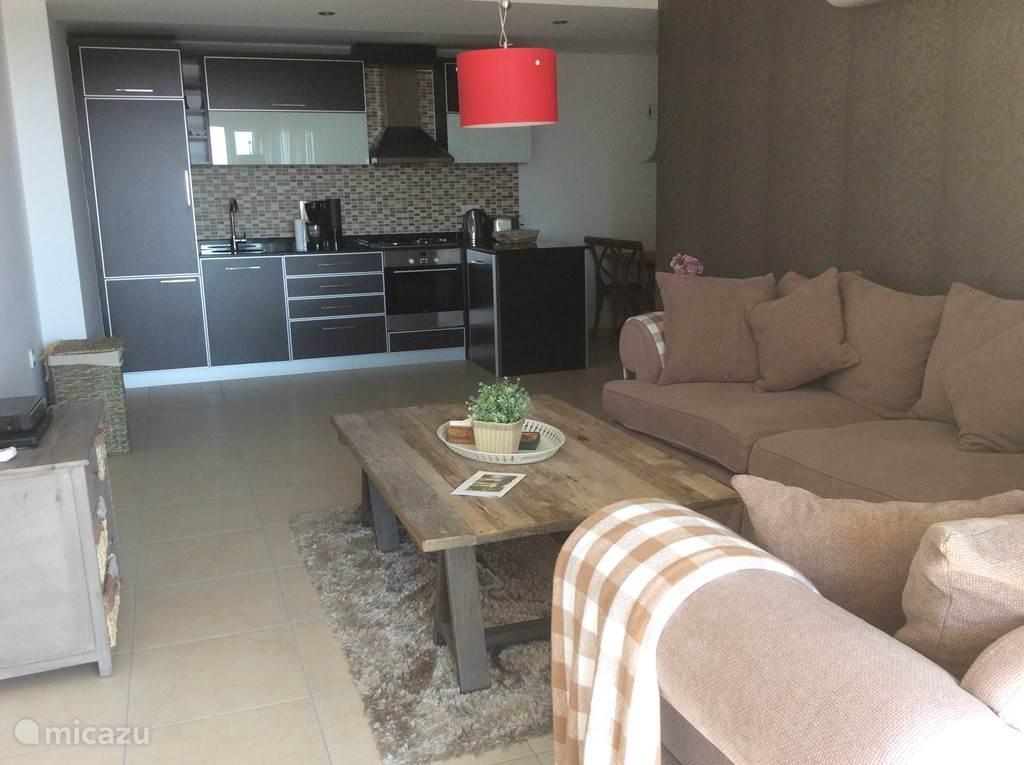 De ruime woonkamer heeft een warme landeljke sfeer en is via een grote glazen schuifdeur met het terras verbonden.