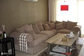 Een heerlijke woonkamer met ruim zitgedeelte en fraaie salontafel. Philips Flatscreen, sateliet-receiver en dvd-player.