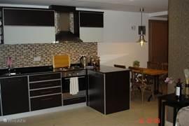 De open keuken is opgebouwd uit Siemens apparaten, afgwerkt in donkerbruin hout met zwart granieten werkblad.