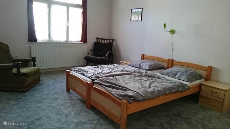 Slaapkamer met lits-jumeaux en twee fauteuils.