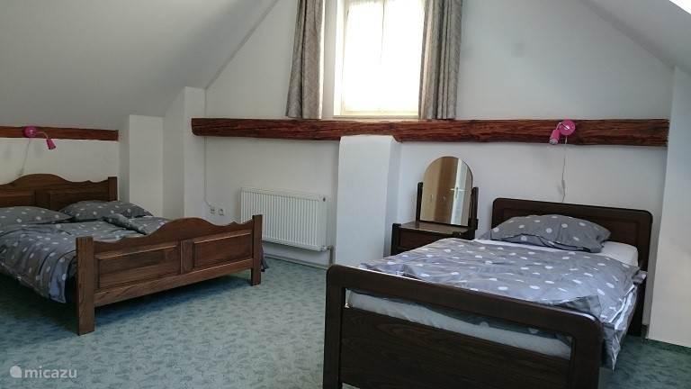 Slaapkamer boven met tweepersoonsbed, een eenpersoonsbed en kaptafel.