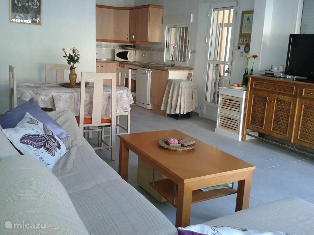 Ruime woonkamer met eettafel en bankstel.De woonkamer is verder voorzien van airco.Op de begane grond bevindt zich tevens een toilet en de wasmachine in de uitbouw.