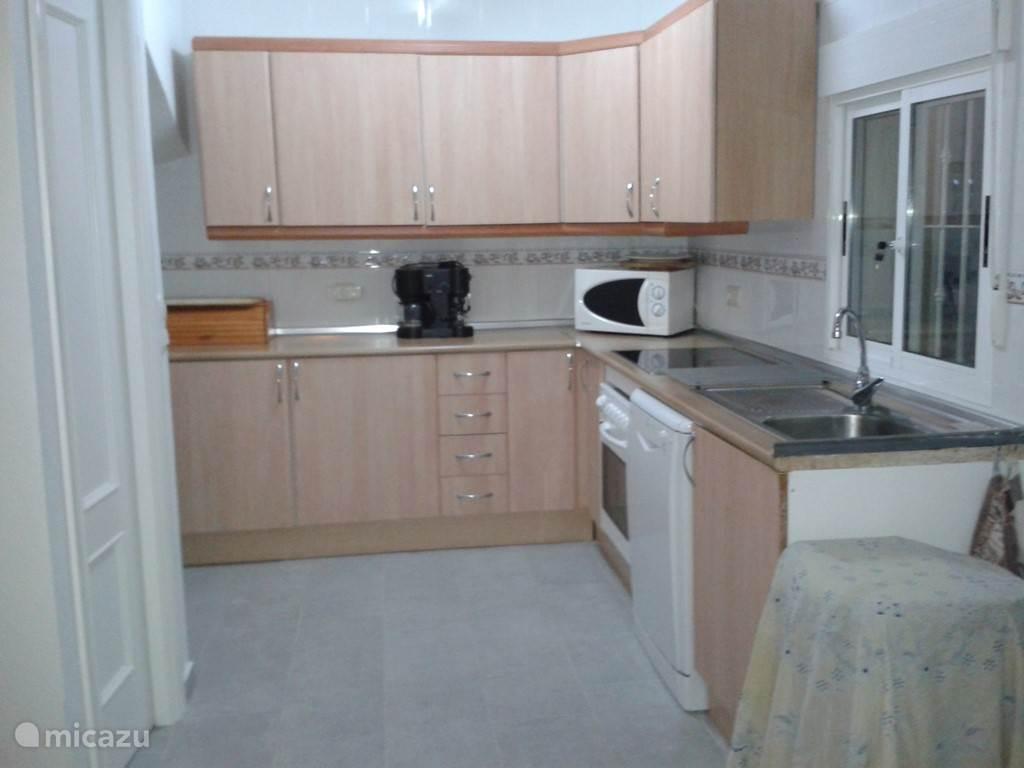 Half open keuken voorzien van oven, keramische kookplaat, vaatwasser, waterkoker.