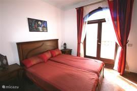 Ein Schlafzimmer mit Doppelbett mit Terrassentüren zum Balkon.