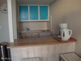 keuken met waterkoker, koffiezetapparaat koelkast, magnetron en houten bar en 2 barkrukken.