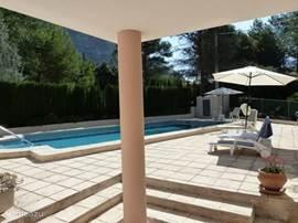 Vanaf het overdekt terras zicht op het zwembad en rechts op een van de terrassen.