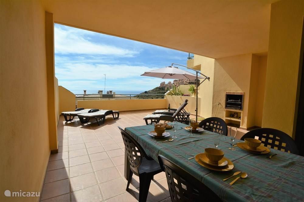 Deels overdekt, beschut en zonnig terras van 49m2 voorzien van buitentafel en 4 ligstoelen met comfortabele kussens. Ingebouwde barbecue. Uitermate geschikt voor overwinteren