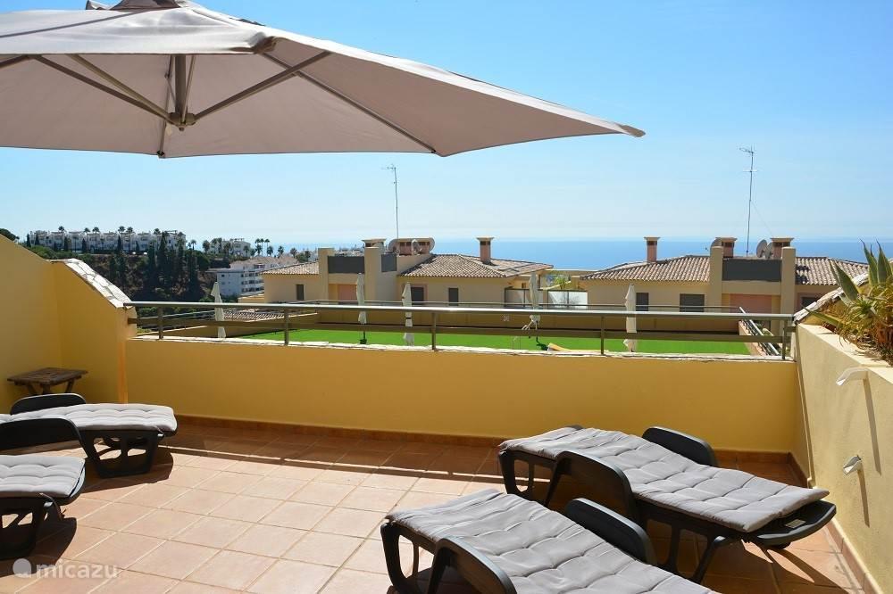 Groot en zonnig terras met zicht op zwembad, zee en omringende heuvels