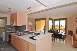 Open keuken met bar van alle gemakken voorzien zoals oven, vaatwasser en bijkeuken met wasmachine.