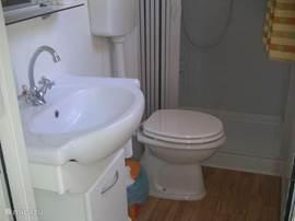 De badkamer heeft een ruime douche van 1m op 1,20 m. Er is ook een toilet en een lavabo met opbergkastje en spiegel aanwezig.