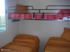 De tweede slaapkamer met 3 eenpersoonsbedden.