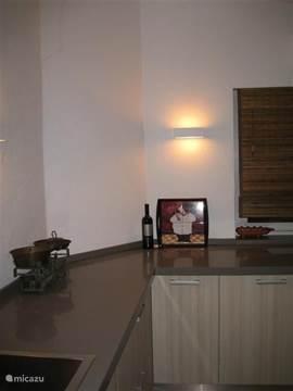De keuken is ruim, heeft een kookeiland en een groot werk oppervlak rondom met 2 spoel gedeeltes.