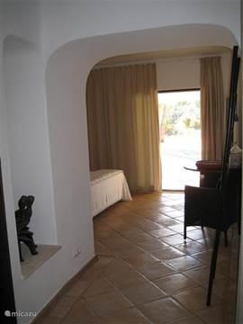 De grote slaapkamer van de villa heeft een ensuite badkamer en inloopdouche. Toegang en uitzicht op de tuin met zwembad.