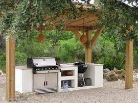 De buitenkeuken met 2  barbecues. Een weber houtskoolgrill en een weber gasgrill-oven-rotisserie.
