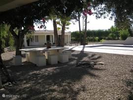 Het met bougainville overgroeit terras van de woonkamer van de villa met blik op het gastenhuis.
