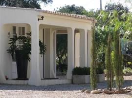 Het gastenhuis bevindt zich op ong. 25 meter van de villa.Het gastenhuis heeft een woonkamer met een gezellig zitje met open haard. De slaapkamer heeft een ensuite badkamer met inloop douche. Het 2-pers. bed, 1.80m x 2m. is een boxspring met orthopedische matrassen.