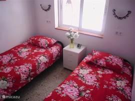 Kleinere slaapkamer met 2 aparte een persoonsbedden, met ruime 2 deurs kast.