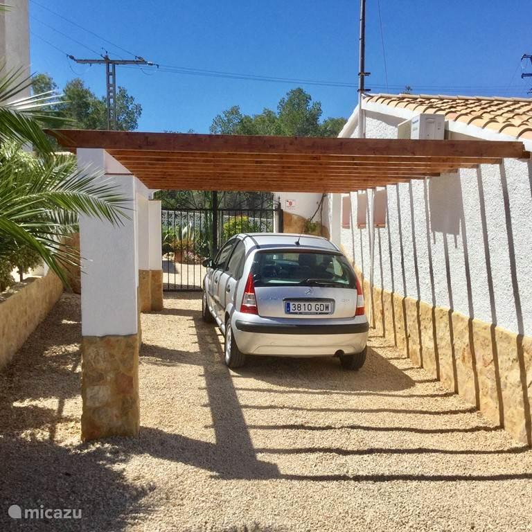 Carport met toegangshek naar achtertuin.