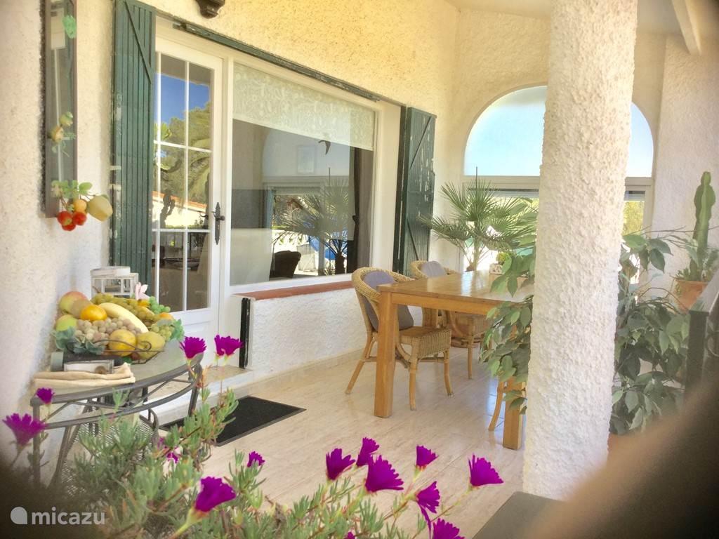 Dit overdekte terras met royale eethoek geeft u een prachtig uitzicht op de voortuin ,met o.a. palmbomen