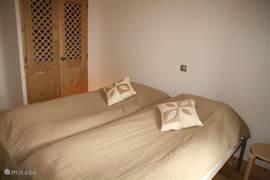De 2e slaapkamer, nu met de bedden opgemaakt als lits-jumeaux. De kamer beschikt ook over een ruime kast. In deze kast vindt u ook het camping bedje met matras.