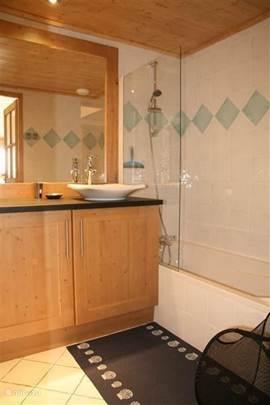 De grootste badkamer heeft een bad en douche