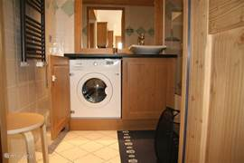 De wasmachine is keurig weggewerkt in de badkamer.