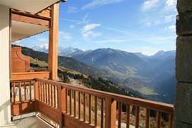 Het zonnige en adembenemende uitzicht van het balkon. Links de Mont Blanc, rechts de vallei van Beaufort
