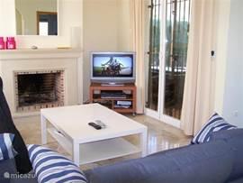 De strak ingerichte huiskamer heeft een flat screen tv, vervangen door een nieuwe tv. WIFI en een comfortabel bankstel. De openslaande deuren geven toegang tot de veranda, tuin en zwembad. Verder heeft deze villa centrale verwarming en een open haard,  voor de kille avonden bij overwintering.