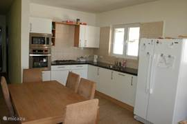 luxury kitchen with granite worktops and appliances including oven, microwave, dishwasher and fridge freezer