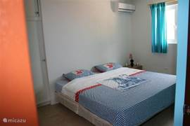 Bedroom with a king size bed with air conditioning and a large built-in wardrobe.