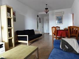Achterin de kamer is rechts de keuken. In het middan van de kamer ga je naar de 2 slaapkamers en badkamer.
