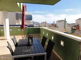 Groot balkon 16m2 met uitzicht over Benidorm en de zee. Grote houten eettafel met stoelen. Grote parasol.