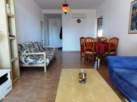 Langwerpige woonkamermet 2 banken, flat tv. en ronde eettafel.
