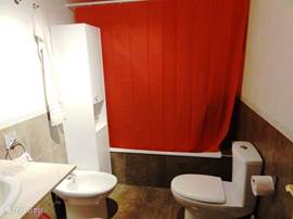 Badkamer met ligbad/douche, toilet, bidet en wastafel. De badkamer ligt tussen de 2 slaapkamers in.