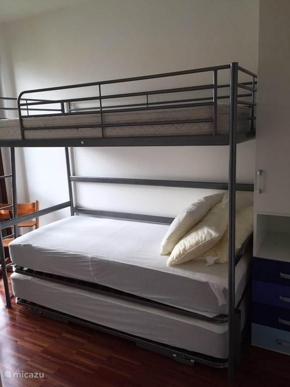 Slaapkamer met drie 1-persoonsbedden, openslaande raamdeur en kastruimte. Het ondergeschoven bed kan naast het andere bed geplaatst worden